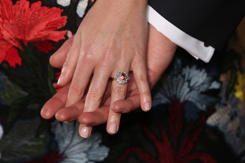 Britain's Princess Eugenie of York (L), displays her engagement ring containing a padparadscha sapphire surrounded by diamonds, as she poses with her fiance Jack Brooksbank in the Picture Gallery at Buckingham Palace in London on January 22, 2018, after the announcement of their engagement.