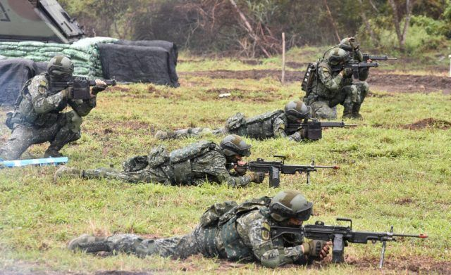 Soldiers take aim with their weapons during an annual drill at the a military base in the eastern city of Hualien