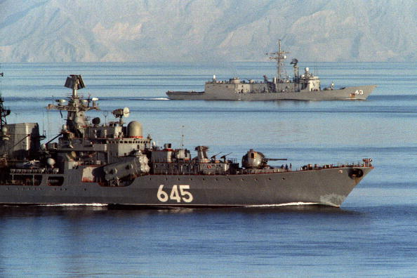 A Soviet warship passes alongside the U.S. guided missile frigate USS Thach
