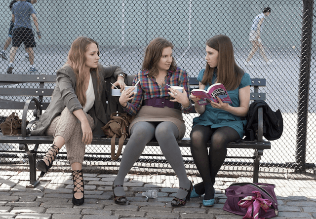 'Girls' cast sitting on a park bench.
