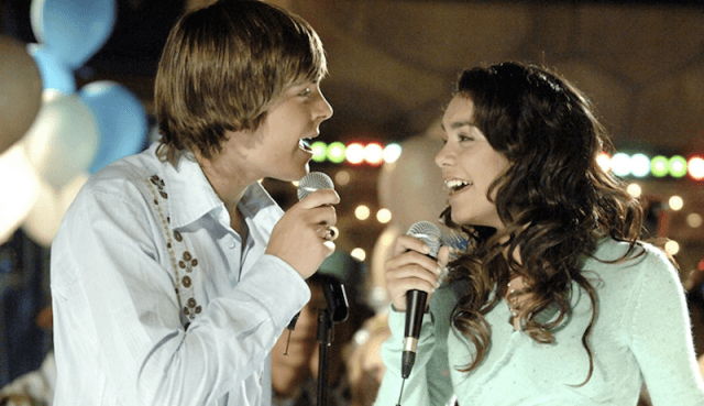 Troy and Gabriela sing into microphones at a party.