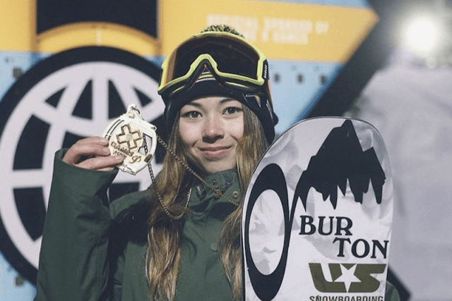 Hailey holds a gold medal while holding a snowboard.