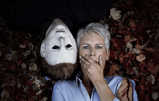 Jaime Lee Curtis laying on a ground of leaves next to a strange figure in 'Halloween'.