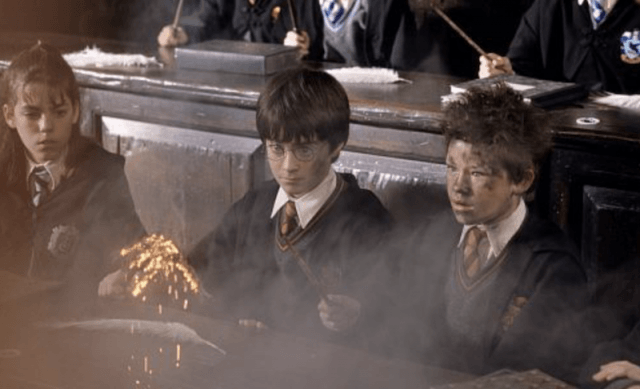 Harry Potter and his classmates sitting in row watching a feather combust.