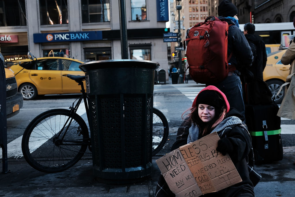 A young homeless woman panhandles on the streets of Manhattan