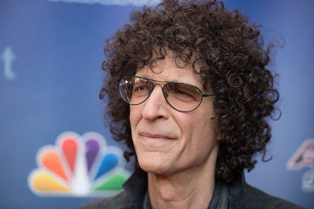 Howard Stern poses on a red carpet at an NBC event.