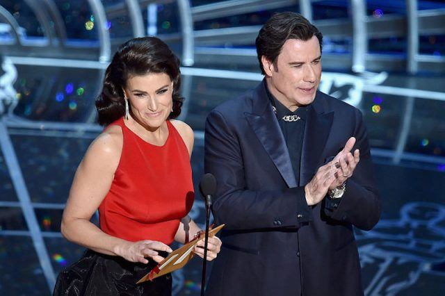 Idina Menzel accepting an award as John Travolta applauds.