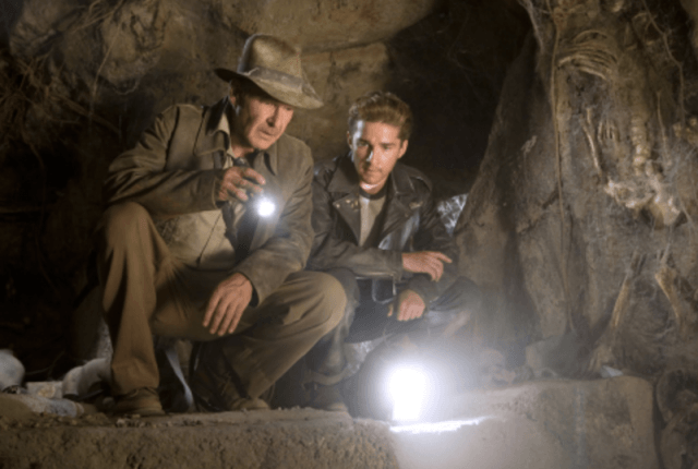 Two men inspecting the ground with a flashlight.