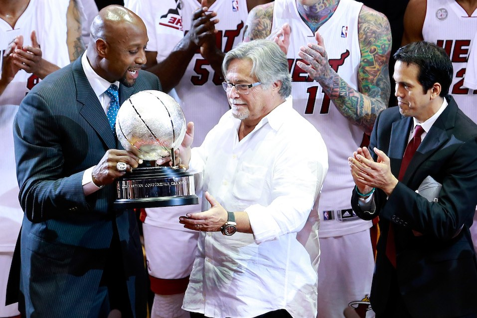 Former Miami Heat player Alonzo Mourning presents the Eastern Conference Championship trophy to team owner Micky Arison
