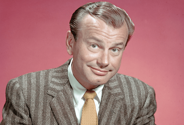 Jack Paar smiling in a suit in front of a pink wall.