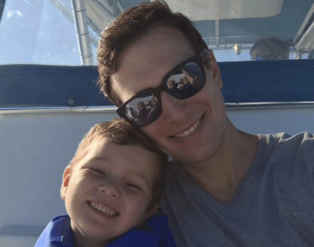 Jared and his son smiling while sitting on a boat.