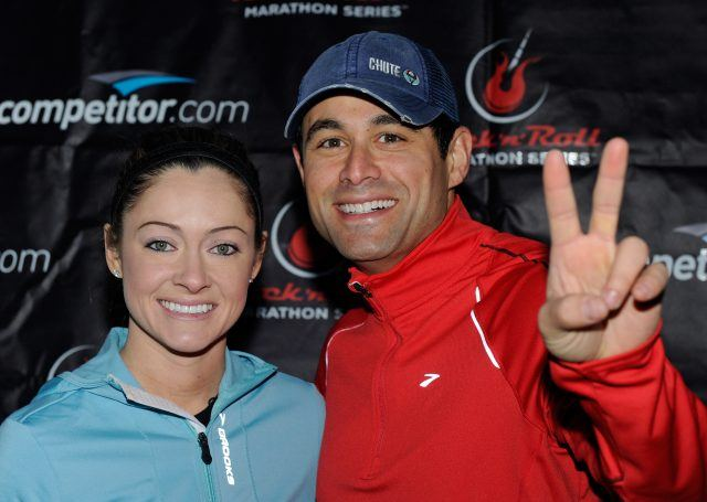 "Molly Malaney smiles as Jason Mesnick grins and holds up a ""peace"" sign with his fingers."
