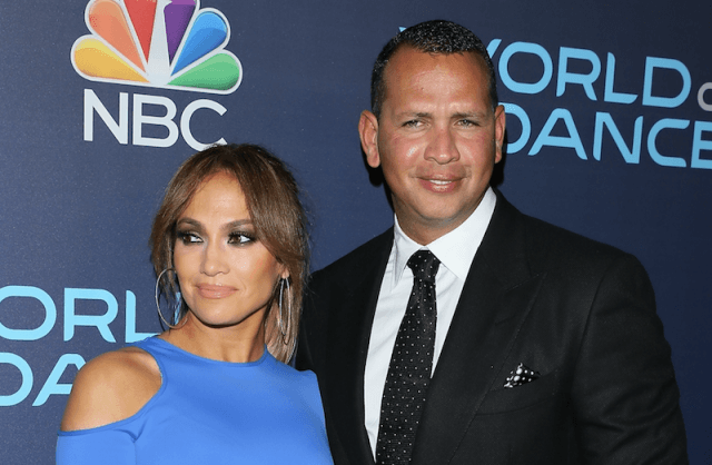 Jennifer Lopez standing next to Alex Rodriguez on a red carpet.