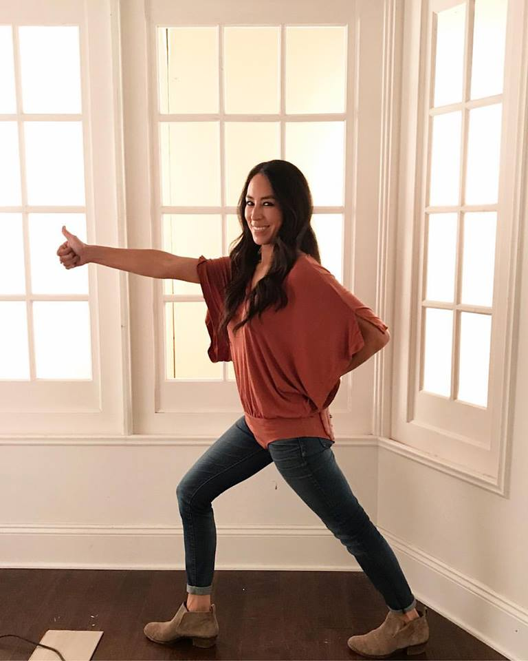 Joanna Gaines with her bodysuit buttoned over her jeans holding a thumbs up.