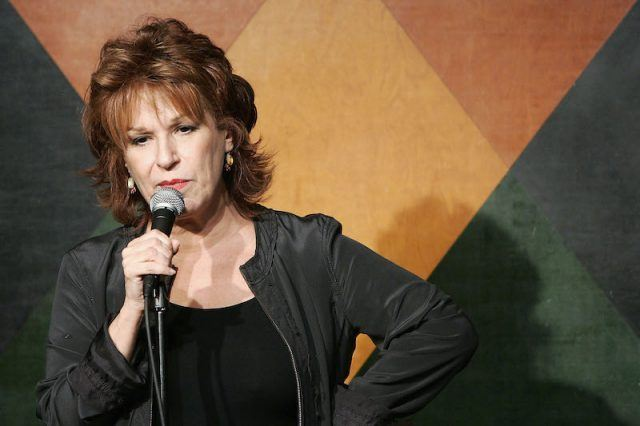 Joy Behar performing while holding a standing microphone with her right hand.