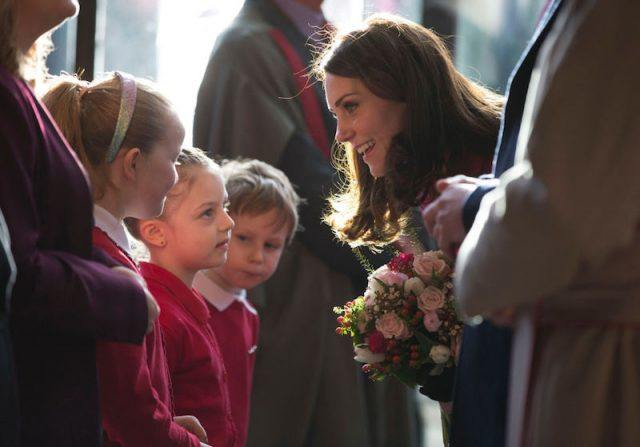 Kate Middleton greeting a group of children.