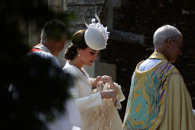 Kate Middleton holds Princess Charlotte as she walks into a church.