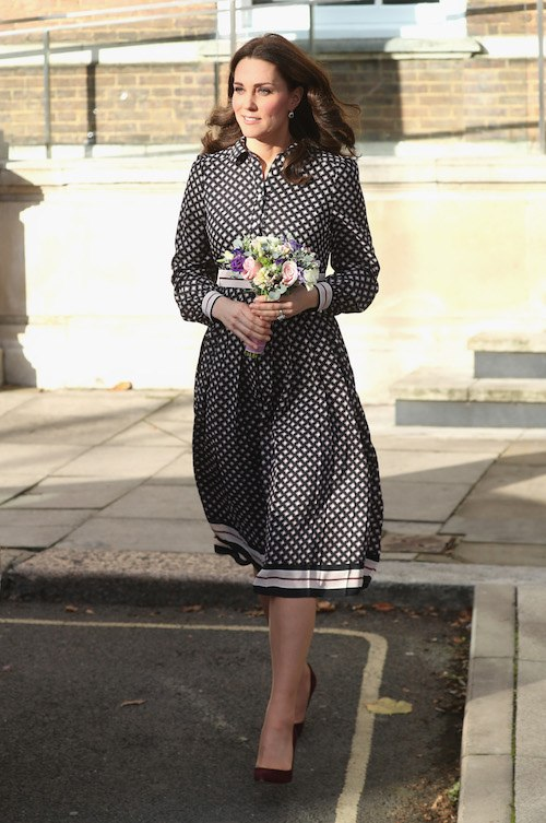Kate Middleton walking with a bouquet in her hands.