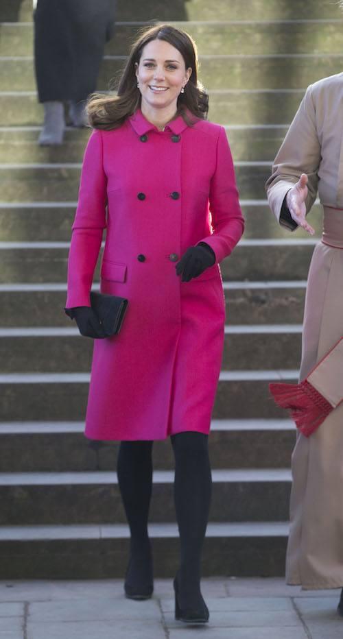 Kate Middleton walking in a pink coat.