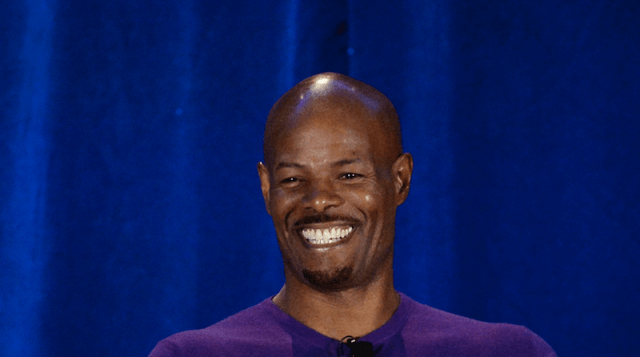 Keenen Ivory Wayans in front of a blue curtain.