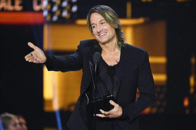 Keith Urban holding an award as he points at the audience.