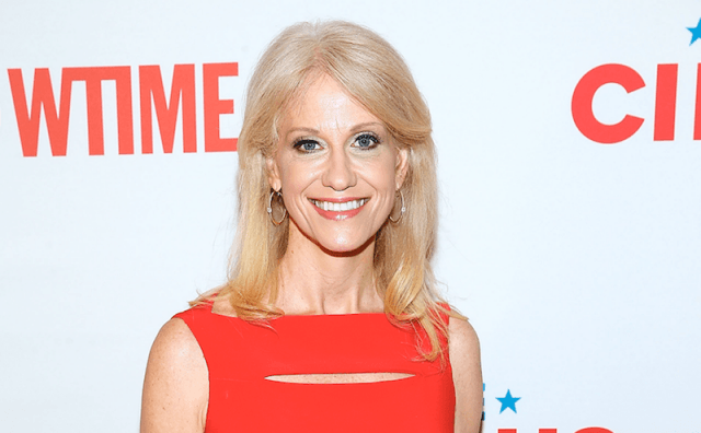 KellyAnne Conway smiles as she poses for the paparazzi in a red dress.