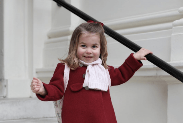 Princess Charlotte holds a railing as she climbs down a staircase.