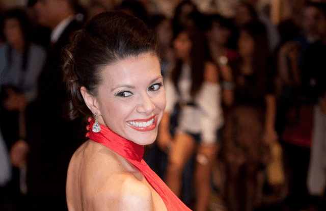 Kiran Chetry smiling in a red dress.