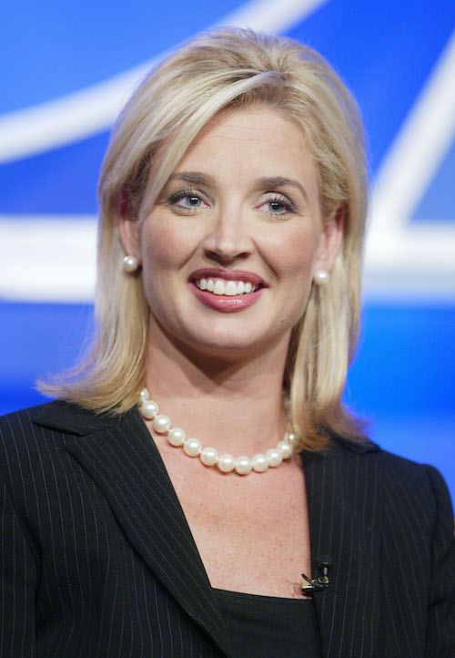 Laurie Dhue smiling while wearing a black top and white pearls.