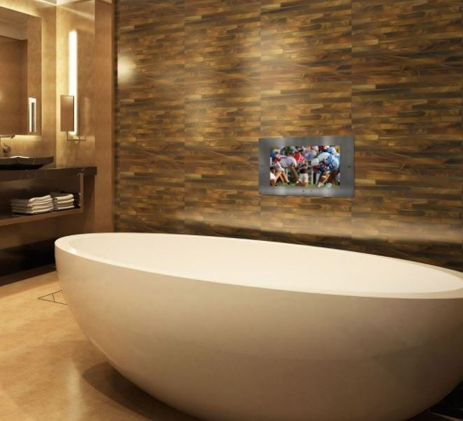 A Lightology Mirrored Waterproof TV installed above a bathtub