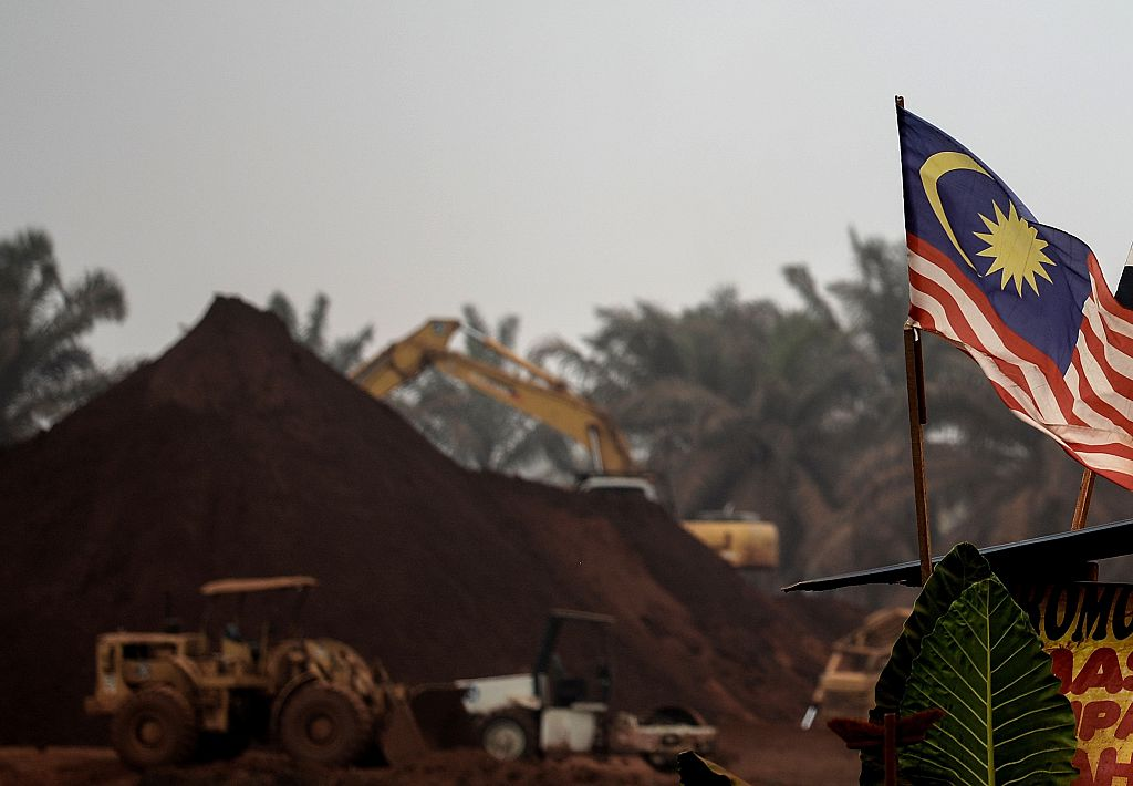 a Malaysian flag flies at the entry-point to a Bauxite mining site in Bukit Goh situated in Malaysia's rural state of Pahang