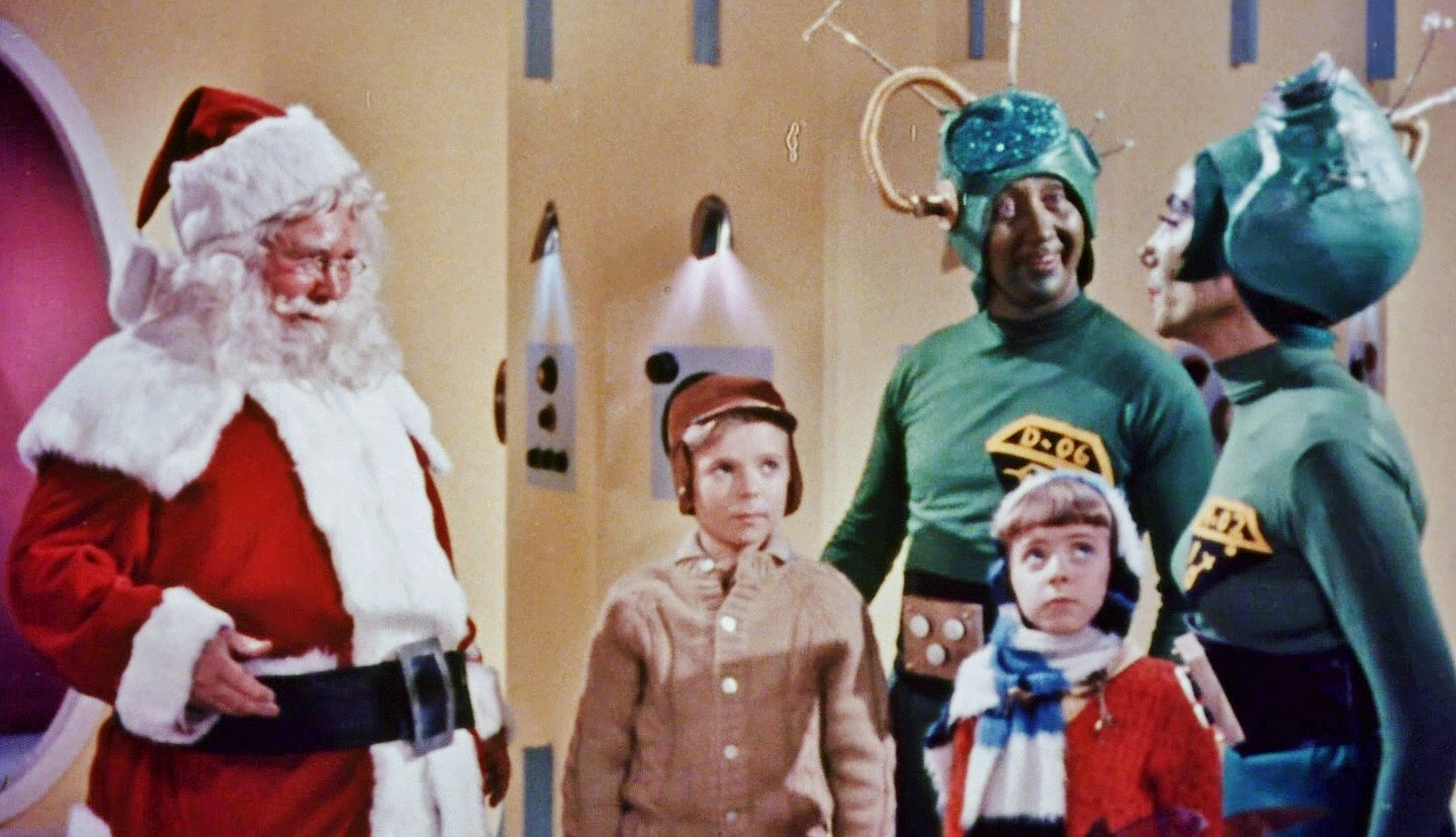 Santa talks to two people in martian outfits