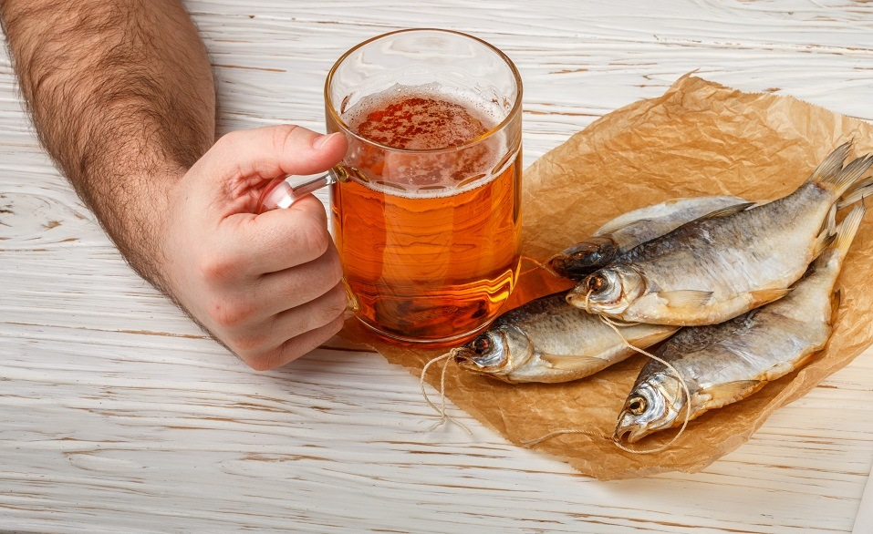 Male hand with a glass of beer and dry fish