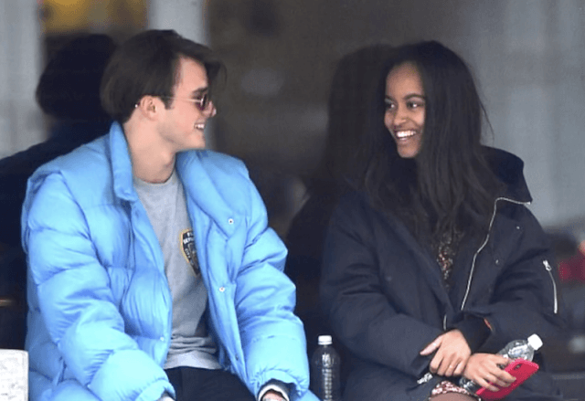 Rory and Malia laughing while sitting together.