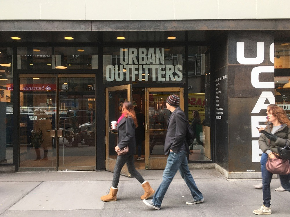 Man and woman walk passed Urban Outfitters