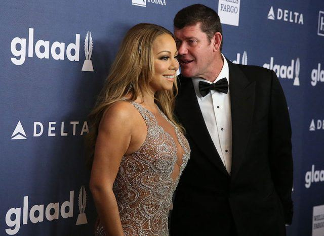 Mariah Carey posing with James Packer on a red carpet.