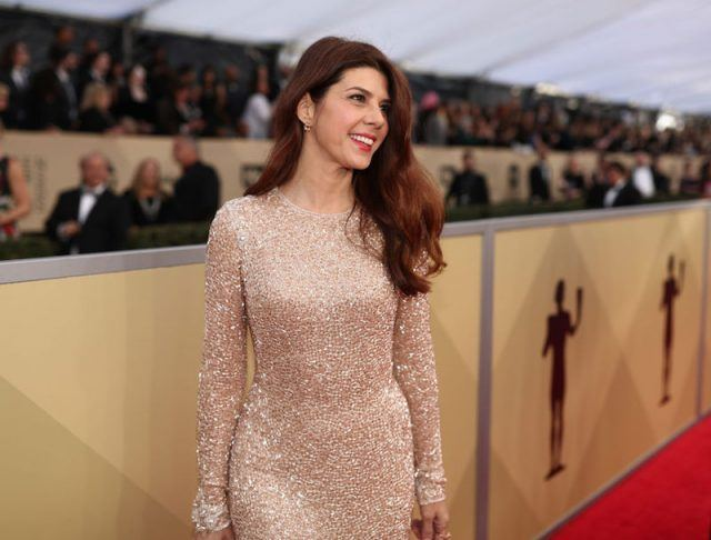 Marisa Tomei smiling while wearing a sparkly dress on a red carpet.