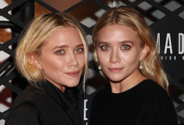 Mary-Kate Olsen and Ashley Olsen posing together while dressed in matching black outfits.