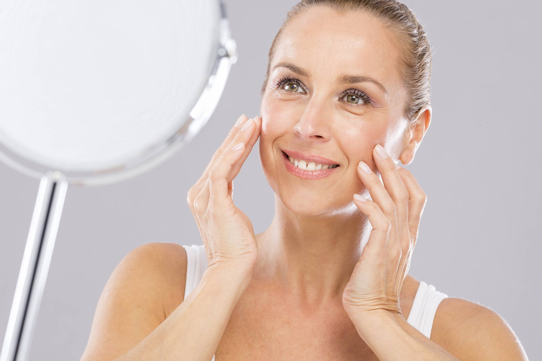 Mature woman applying moisturizer to her skin in a mirror