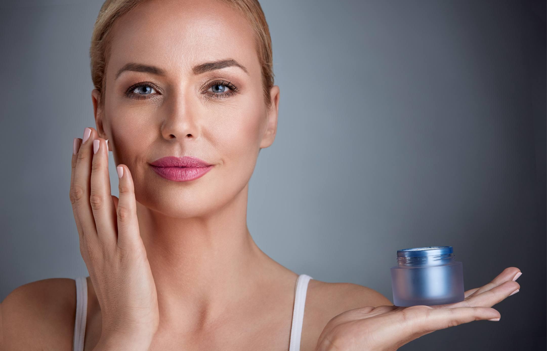 Woman applying moisturizing cream to her skin