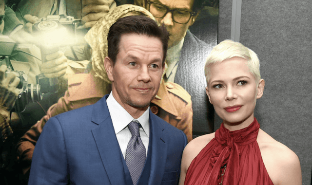 Mark Wahlberg and Michele Williams posing together in front of a movie poster.