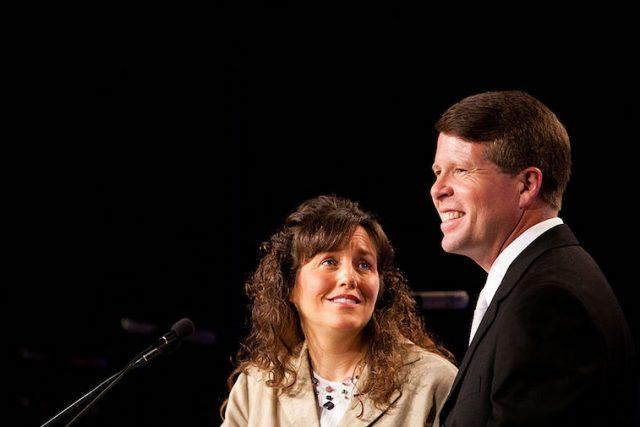 Michelle and Jim Bob Duggar speaking in front of a microphone.