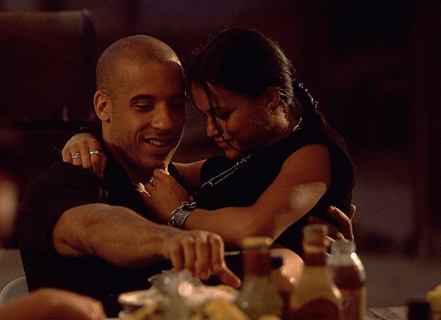Letty sits on Dominic's lap and wraps her arms around him as they sit at a table.