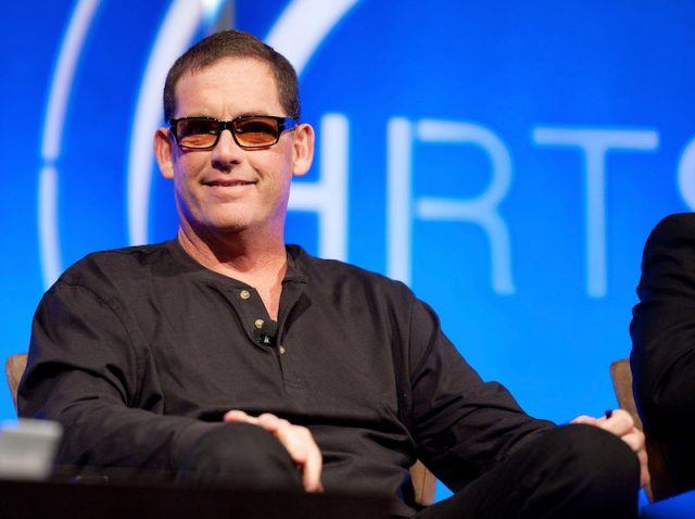 Mike Fleiss sits in a chair on stage during a panel interview.