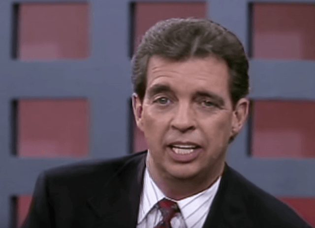 Morton Downey Jr. wearing a suit and tie on a talk show.