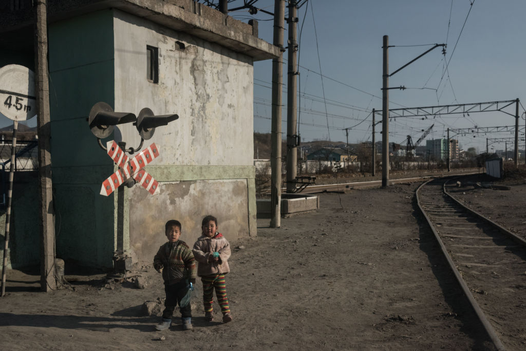 Children stand besides a railway track in the industrial city of Chongjin on North Korea's northeast coast