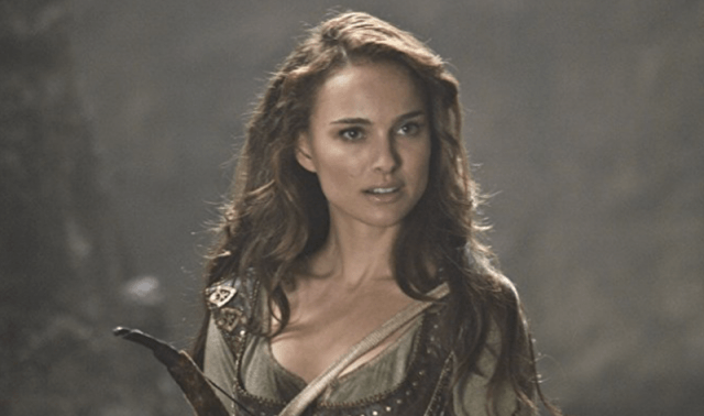 Natalie Portman holds a bow and arrow while standing in a forest.