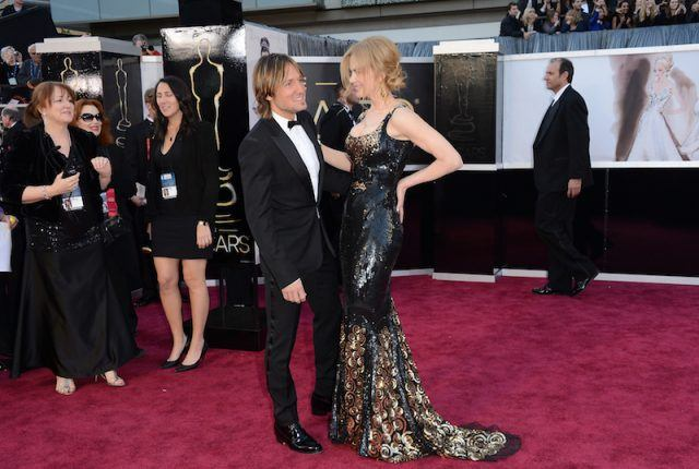 Nicole Kidman and Keith Urban speaking to each other closely as they stand on a red carpet dressed in a black tuxedo and gown.