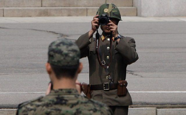 A North Korean soldier looks through a camera.