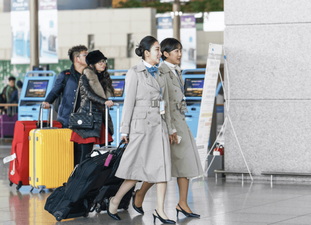Two women walk together in an airport.